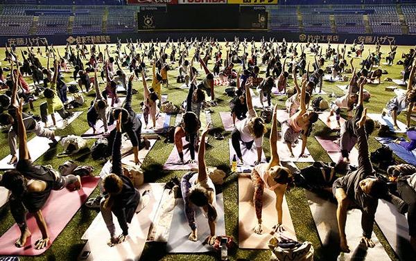 又现运动者抢足球地盘 数百名瑜伽爱好者足球场秀技